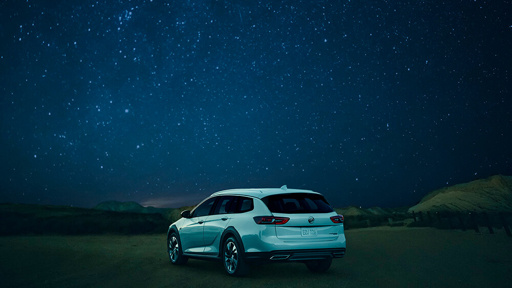 White SUV under a starry night after a night drive