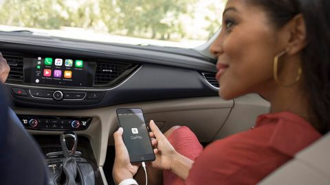 Woman in car accessing CarPlay on smartphone