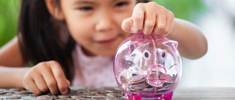 Little girl adding money to a piggy bank