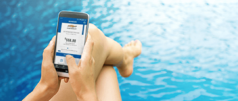 woman relaxing by the pool with GM Financial Mobile app displayed on phone