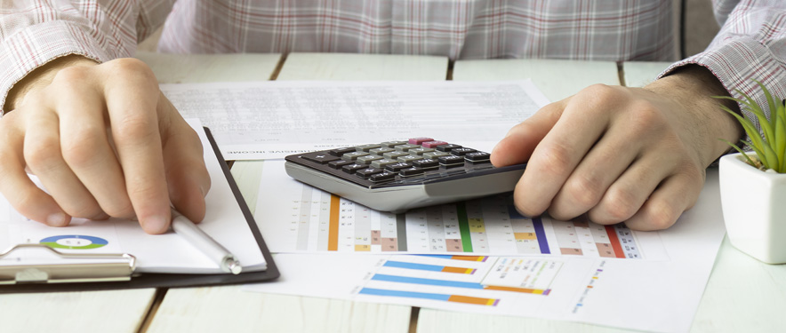 Man with calculator and budgeting sheets at a table