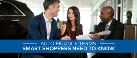 Salesperson and customers discussing auto finance terms at dealership